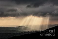 The sun rays pass through clouds, creating the most varied forms that illuminate the hills below and the surrounding mountains. Photographed from a small town called Elcito in the park of Monti San Vicino and Canfaito, Italy. End of October 2016