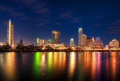 Austin Texas skyline.  The effects of the evening lights create a beautiful rainbow of colors on Ladybird Lake.