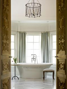 There's nothing dreamy or luxurious about a standard ceiling light in the bathroom. Learn how designers take bathrooms from blah to brilliant with the use of chandeliers, decorative wall sconces, perimeter and recessed lighting.
