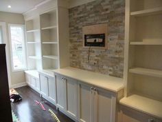 Gorgeous white built in with tile/stone behind tv!