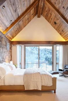 Aspen, Colorado bedroom; rustic; stone walls; vaulted wooden ceiling; modern Eames lounge chair and ottoman