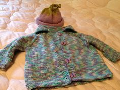 Knitted baby sweater and matching grape hat.