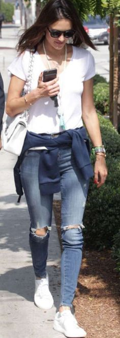 Who made  Alessandra Ambrosio's white quilted handbag, white tee, skinny blue jeans, sneakers, and sunglasses?
