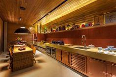 Inspirado nas cozinhas das fazendas do interior, a área de cocção do Atelier Gourmand conta com fogão a lenha, forno de pizza e churrasqueira (ao fundo). Nos revestimentos, o cimento queimado amarelo e vermelho foi combinado ao painel de madeira que sobe a partir do terço superior da parede e recobre o forro. O espaço assinado pela decoradora Denise Vilela foi exposto na edição 2013 da Casa Cor MG