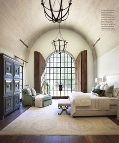 Gorgeous bedroom with arched ceiling an gorgeous arched window with shutters.