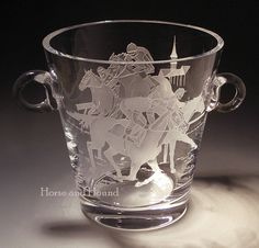 Clubhouse Turn Wine Bucket. This impressive etched crystal container can double as a ice bucket or a spectacular centerpiece flower vase. Heavy European crystal deep etched with Thoroughbred racehorses and jockeys both front and back with a clubhouse spire in the background.