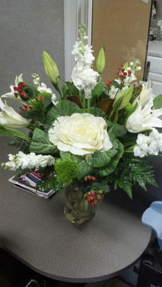 Lovely Casa Blanca Lillies, fragrant white Stock, unique green Trixx Carnations, and red Hypericum are complimented by a large snowy white Ornamental Cabbage. This Custom Vase arrangement is sure to please