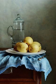 Classic still life with few yellow Asian Pears on blue folded napkin and tall pitcher with water in old kitchen                                                                                                                                                      More