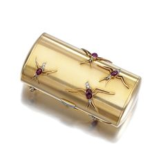 RUBY AND DIAMOND VANITY CASE, CARTIER, CIRCA 1950.The cylindrical case applied with swallow motifs set with a cabochon ruby and circular-cut diamonds, opening to reveal two compartments, mirror and aide memoire, signed Cartier Paris