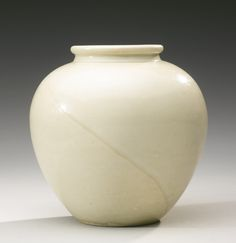 A 'XING' WHITE-GLAZED JAR  TANG DYNASTY rising from a flat base to wide rounded shoulders and curving in sharply at the short upright neck with wide rolled mouthrim, applied overall with a fine milky-white glaze pooling to a greenish tint around the neck and stopping just before the foot