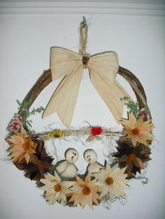 Guirlanda confeccionada com base de cipó, pássaros e flores confeccionados palha de milho em tons de bege....