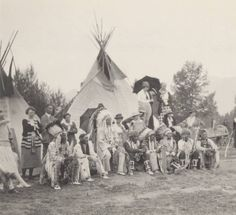 """1920.  Blackfoot Indians, wearing headdresses and traditional regalia, gather with others in front of two painted tipis . Natives identified as  """"Raven Chief""""; """"Yellow Wolf's holding scabbard""""; """"Wades in the Water with Lone Wolf's shirt 1920""""; """"Oscar Boy""""; """"Celia's Last Star first husband""""; """"n.b. knife sheath."""""""