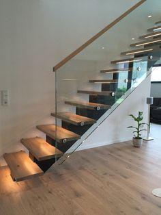 Mittelholmtreppe mit Holzstufen und Glasgeländer. LED Beleuchtung