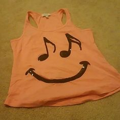 Coral Racer back tank Has smiley face made of notes on the front. Was a hand me down so I don't know how much it has been worn Delia's Tops Tank Tops