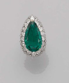 A fine emerald ring/pendant by Harry Winston.The pear-shaped emerald weighing 16.32 carats within a pear-shaped and brilliant-cut diamond surround, detaching to form a pendant. Ring mount signed Winston and with maker's mark of Jacques Timey for Harry Winston.
