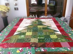 This is my design of the christmas tree quilt.  I decided not to do a rag quilt but liked the cleaner look of a regular top. I tied the three layers together using gold and silver [string] I found. Nevermind the vinyl dancing santa tablecloth it is resting on - I was at my mother's house.