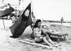 An American beach-goer doesn't want to be mistaken for Japanese when she sunbathes on her days off, so she brings along a Chinese flag.