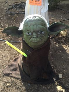 Star Wars Yoda Pumpkin head. Cut out foam craft sheets to create ears and hot glue to sides of pumpkin. Remove pumpkin stem & spray paint sage Green. Use acrylic paints for face and ear details. Use lighter yellow greens for highlights to create depth. Use halloween cob webs for fuzzy hair effect. Place on an upside down 5 gallon bucket with hole cut into bottom to support head. Complete look with burlap drape & light saber! May the force be with you this Halloween!Vote for us by sending #29…