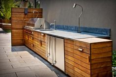 This custom outdoor kitchen is complete with brushed stainless steel appliances, plenty of counter space and wooden cabinetry to enhance the modern atmosphere of this New York City backyard.