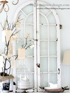A beautiful pair of arched shutter-style windows gracefully sit atop a buffet table...Old Window Ideas For Clever Home Decor