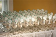 Wedding favors: wine glasses with lyric printed on them and place card sitting on rim of each glass. Guests came in and found their glass to find their seat!