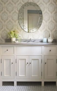 James Michael Howard    Love wallpaper in bathrooms. beautiful, elegant white gray blue bathroom design with white paneled bathroom cabinets against patterned wallpaper is divine. The round mirror is perfect with the vanity! Love the gray counter tops counter tops! Love the marble floor too! Gray white blue wallpaper.