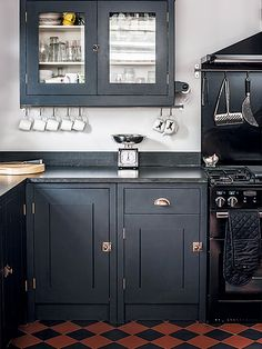 Farrow & Ball's Off Black has been used here on this Shaker-style kitchen for dramatic impact, accented with brushed copper fixtures and complemented by a dark range cooker and checkerboard terracotta tiling.