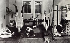 FITNESS: Seven women exercise in a small gym. New York, 1910.