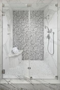 A seamless glass walk-in shower boasts a curved marble shower bench fixed on marble grid floor tiles beneath a tiled niche framed by a marble surround.