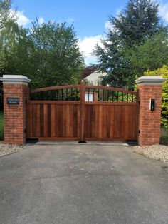 Electric hardwood gate combining the finest iroko timber with metal inserts. Fully automated with visible intercom system.