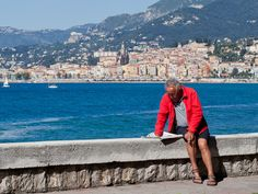 This man is Italian and is reading an Italian newspaper in Italy. In the background is Menton which of course is in France.