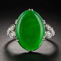 Vintage Jade Platinum Diamond Ring. A bright, happy green oval jadeite of natural color sits snug in this low-profile 1930s vintage platinum and diamond ring designed with glittering diamond-set trefoil shoulders. The back side of the jade displays a carved symbol, perhaps the carvers chop mark, or this piece may have been cut long ago from a larger, more elaborately carved piece. The jade measures 5/8 inches long by 7/16 inches wide