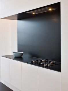 Countertop: thin with no overhang as well as monochromatic backsplash up to undercabinet. Handleless doors