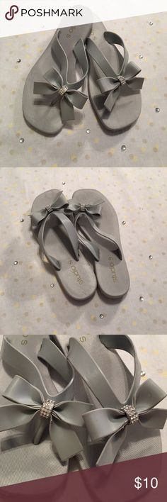 Grey Flip Flops with Sparkle Bow Grey fancy flip flops! They have a slight heal and have a bow with a sparkle ring around it! They are super cute! The strap is bent from storage and I'm sure after being worn it will straighten out. My daughter wore them once on our first cruise, but sadly grew out of them. The shape looks funky, but they look cute on and are the shape of your toes! Studio S Shoes