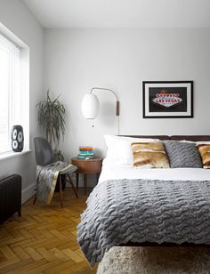 The parquet flooring in the Blacks' bedroom was found in a salvage yard. Beside the bed is a George Nelson Bubble lamp.