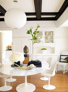 white gray Saarinen marble top dining table Saarinen tulip chairs stone buddha head built-ins hutch buffet oak floors black wood beams dining room Saarinen Table Saarinen Tulip Chair Nelson Ball pendant