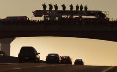Firemen salute from the top of their truck as residents of Port Hope stand below them with flags on a bridge to honor Corporal Nathan Cirillo as the motorcade and hearse carrying his body passes along Highway 401, the nation's 'Highway of Heroes', en route to Hamilton, Ontario October 24, 2014.  REUTERS-Fred Thornhill