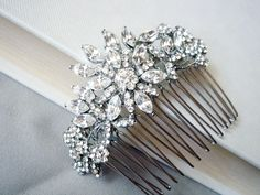 Glittering and gorgeous, this piece is inspired by 1940s hair combs and is perfect for fans of vintage hair accessories. Featuring a stunning floral display of clear Swarovski crystals and sparkly Cubic Zircon stones, with scintillating petals, it's a bold and dazzling statement piece to dress an...