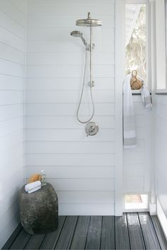This outdoor bathroom accommodates post-swim rinse-offs in rustic style.