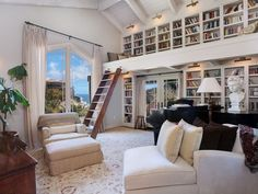 The high vaulted ceiling in this beach-styled white room allows for a full second level of bookshelves. A natural wood ladder allows access to a small loft space filled with pillows for the ultimate in library relaxation.