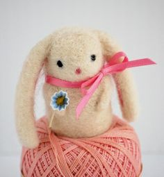 A cream bunny with a blue flower and long ears by Bella Dia
