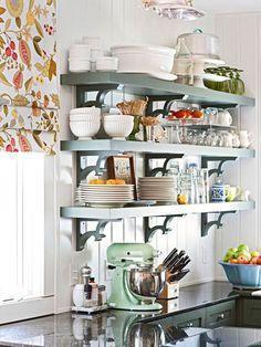 La cuisine a beaucoup de bols et assiettes. Un bol de fruit est sur le comptoir.
