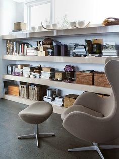 Wonderful textures in this space - the slick finish on the shelves, the storage baskets, and the soft taupe fabric of the egg chair. A heated version of this concrete floor would be great in our basement.