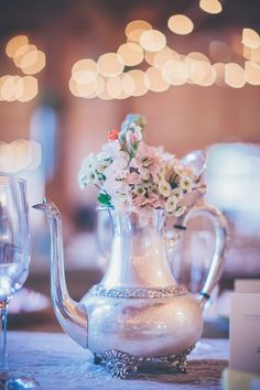 silver pitcher centerpieces, photo by Kris Holland  http://ruffledblog.com/sacramento-barn-wedding #weddingideas #sterlingsilver