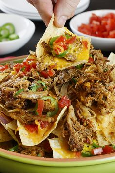 Game day glory starts with this cheesy baked Pulled Pork Nachos recipe. This one-pan game day appetizer is loaded with all the toppings (Think diced tomatoes, kickin' jalapeños, cool sour cream and more.)