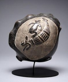 Pre-Columbian, North Coast Peru, ca. 900-1400 CE.  In the shape of a conch Shell, right side depicting a Reed Boat with Jaguar Head as a Prow and a Sea Lion playfully jumping over the Boat; left side depicting a Flying Fish of Large Proportion, maybe a Blue Marlin.