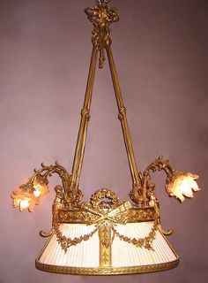A Very Fine and Rare French Belle Époque Gilt-Bronze Figural Chandelier, in the form of a hanging shade surmounted with two Putti on each end, centered with a crossed torches and a laurel wreath crest, with a pleaded silk enclosure and Frosted Glass Shades in the form of flowers. Circa: Paris, 1900