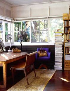 Summer camp feeling. Drafting table. Curved back wood chair. Black. Yellow. Purple. White. Wall of windows.