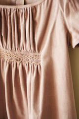 neutral coloured smocking at the waist