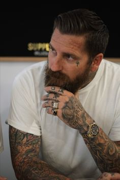 Men's hair. Luke Wessman at a barber shop in lower east side New York called Ludlow barber supply. Beard, tattoos, Rolex and rings. Gentleman
